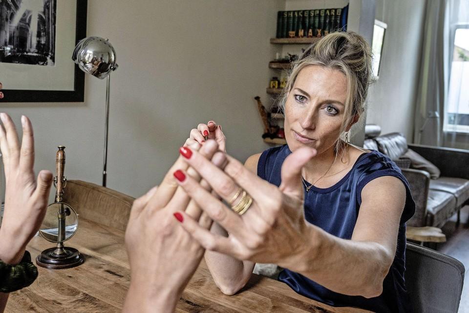 Handanalist en lifecoach Esther Husmann bestudeert de handen van verslaggever Marlies Vording.