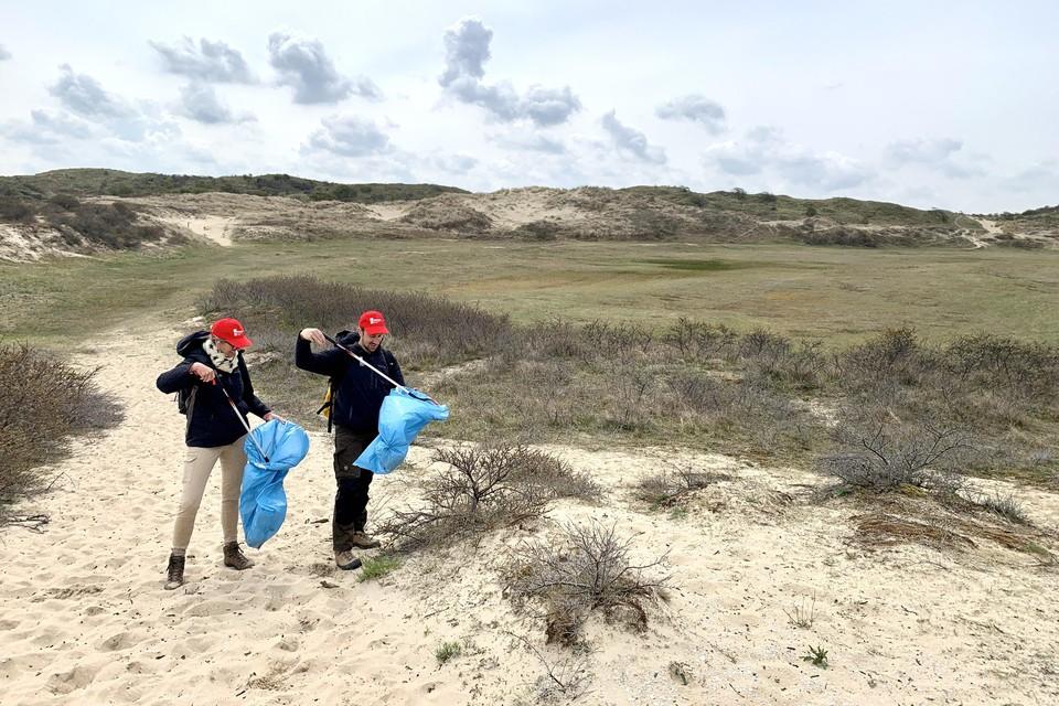 Antje Zender en Tim Rietbergen van Naturalis trekken met knijpstokken de duinen in,