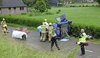 Auto botst tegen lantaarnpaal en belandt op zijkant in Andijk, twee inzittenden met spoed naar het ziekenhuis