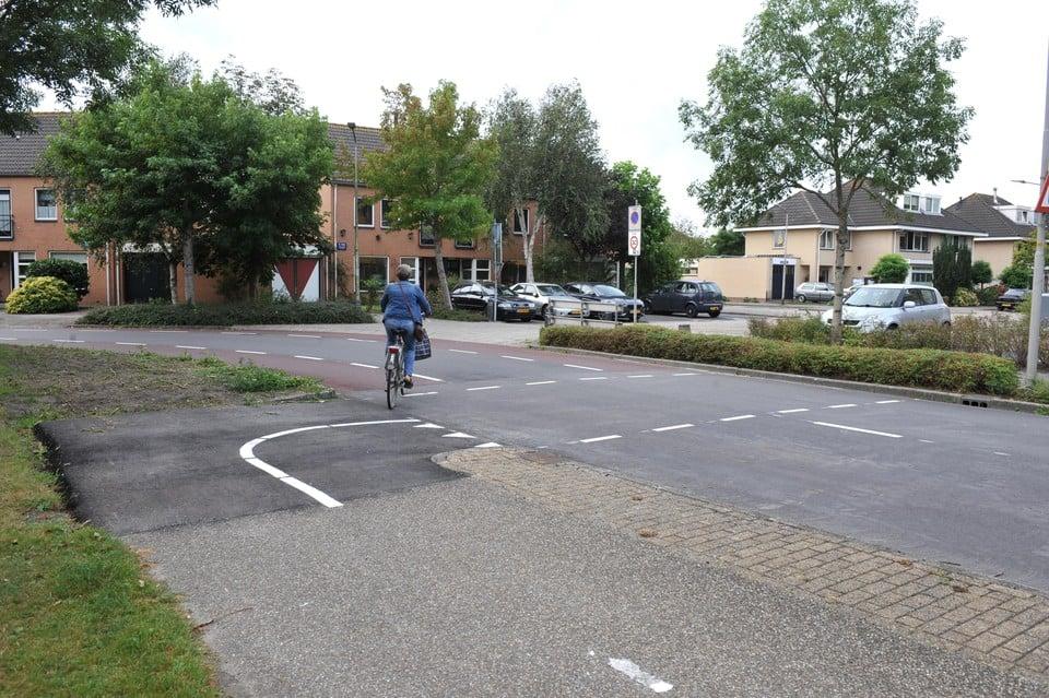 Midden in een bocht van de Anna van Renesselaan in Uitgeest moeten fietsers oversteken, terwijl tegemoetkomende automobilisten geen zicht hebben door een boom en struiken.