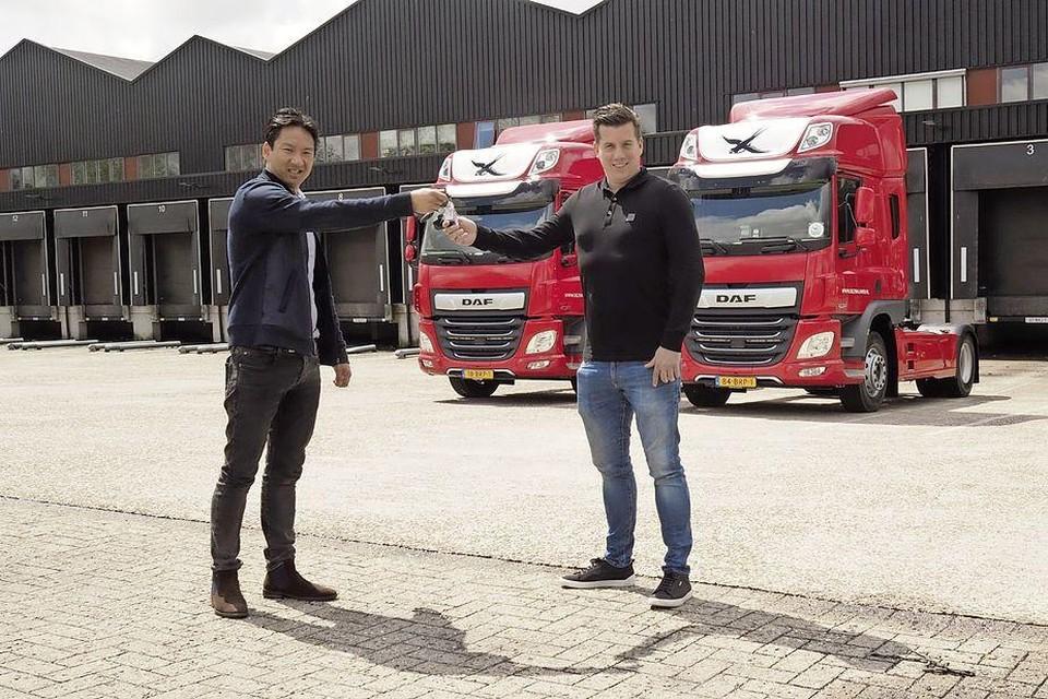 Jeroen Rotman (links) van Truckland overhandigt de sleutels van de twee nieuwe DAF-trucks aan Ferry Bakker van De Zwaluw Logistiek.