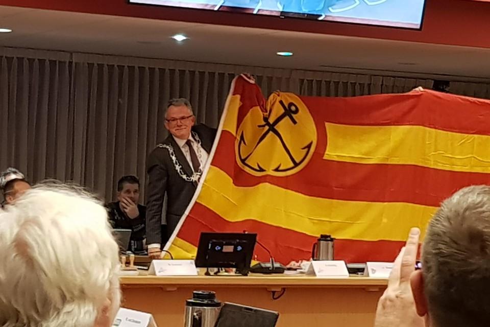 Burgemeester Schuiling ontvouwt de Helderse vlag in de raadszaal.