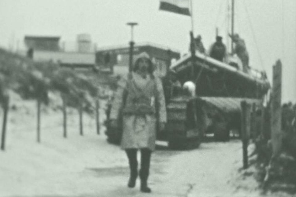 Statig wordt reddingboot Ubbo voortgetrokken over de strandopgang van Egmond aan Zee. Voorop loopt een lid van de bemanning in de zo kenmerkende kleding. Achter de duinen nog net zichtbaar het bekende Lido.