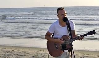 Wat doet die man daar met zijn gitaar en camera's om zich heen op het strand? Nou, zangvideo's opnemen natuurlijk. Josh van den Berg ambieert geen vol Ziggo Dome. 'Ik vind het gewoon leuk om muziek te maken' [video]