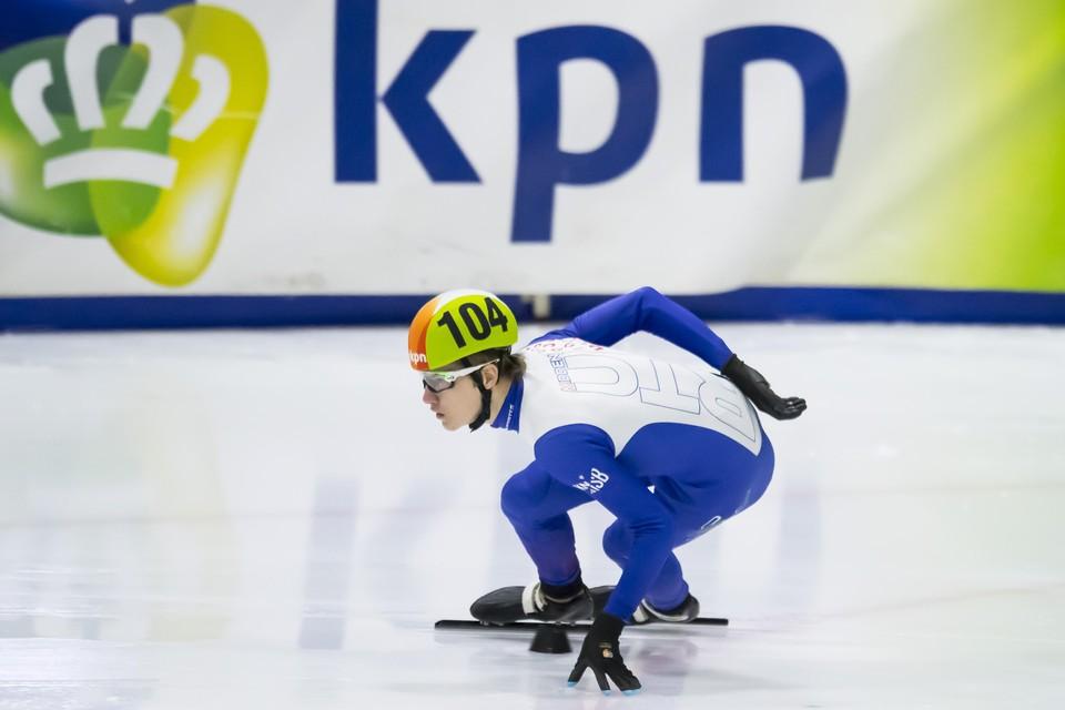 Ingmar van de Griek in de bocht met een hand op her ijs tijdens het NK voor junioren in Utrecht.