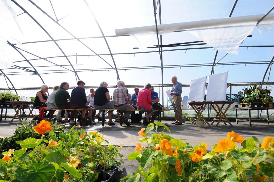 Henk Huibers uit Oudkarspel en een groepje bezoekers van Thuis in een bloemenkas van het bedrijf Preijde. FOTO BUREAU MENEER DE LEEUW