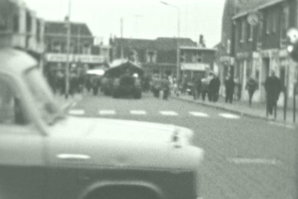 Een auto rijdt nog snel voorbij over de Boulevard Zuid terwijl in de verte de tractor met daarachter de reddingboot aan komen rollen. Vanuit de richting van het Pompplein over de Voorstraat.