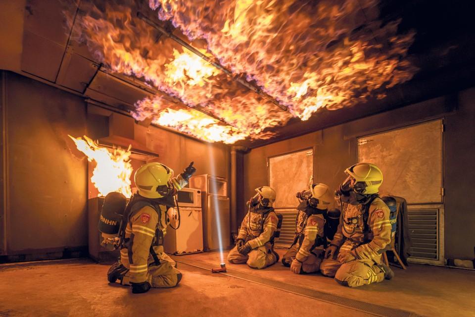 Brandweercursisten bekijken hoe snel vuur zich kan verspreiden.