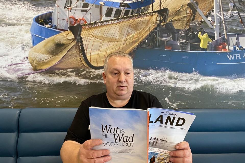 Mark de Greef uit Den Oever bekijkt het eerste exemplaar van 'In Eigen Land' dat geheel gewijd is aan het Waddengebied.