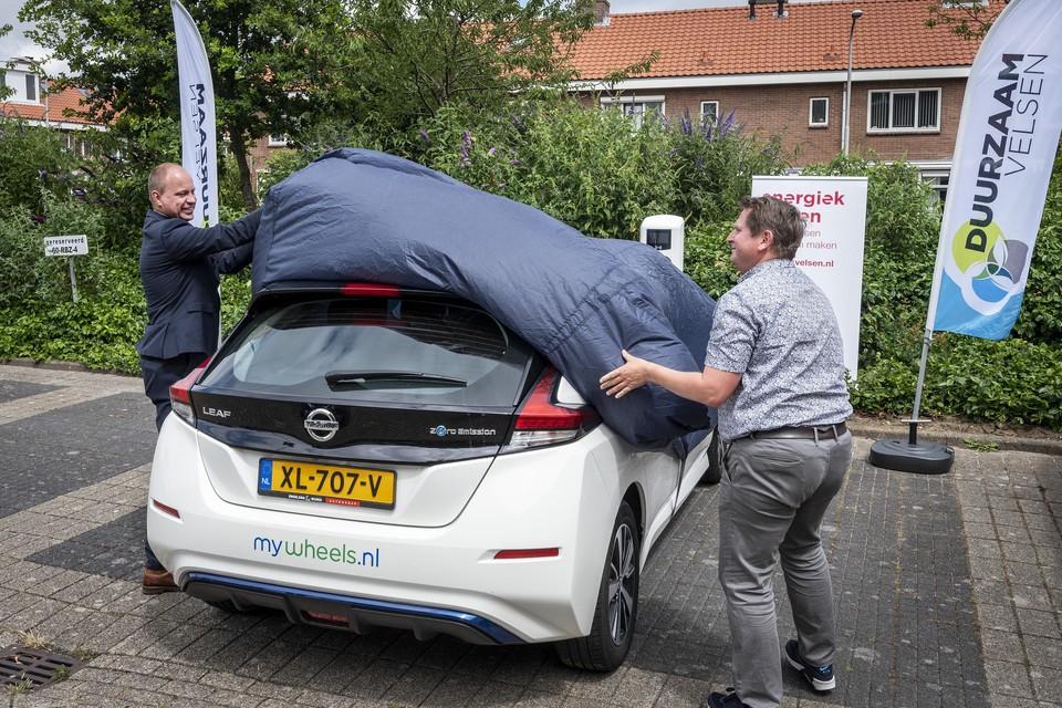 De eerste deelauto van de gemeente wordt onthuld door wethouder Diepstraten en Martijn Mewe van Energiek Velsen.