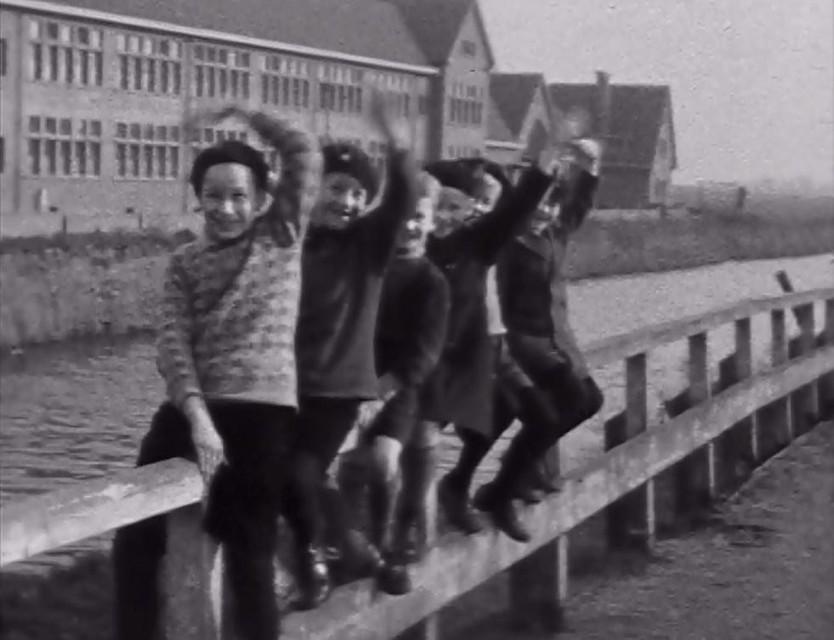 Zwaaiende kinderen kijken lachend in de camera. Het hek waar ze op zitten, staat langs de Meester P.J. Troelstrakade, gezien vanaf de Blekerskade. Op de achtergrond het gebouw van het Petrus Canisius Lyceum. Daar weer achter de weilanden.