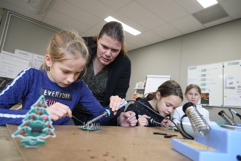 Kinderen op De Wingerd in Zwaag solderen printplaatjes die uiteindelijk in kerstboompjes resulteren met knipperende lampjes.