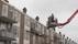 Man zit met knie vast in balkonhek, brandweer schiet te hulp met hoogwerker