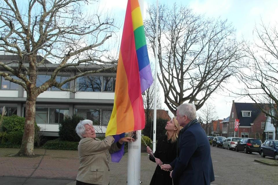Burgemeester Anne Lize van der Stoel (links) en de wethouders Mandy Elfferich en Richard Quakernaat hijsen de regenboogvlag.