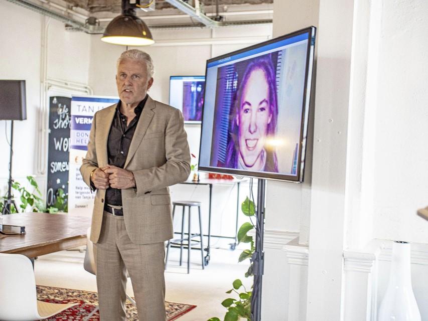 Peter R. de Vries met naast hem het scherm waar het gezicht van Tanja Groen op wordt getoond.