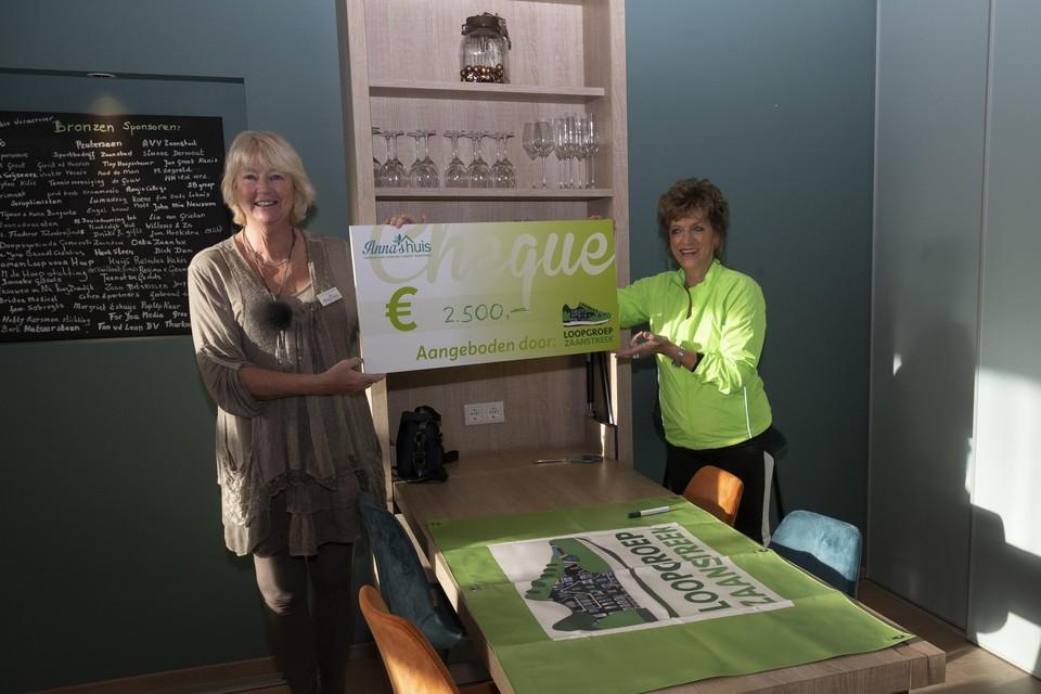 Sylvia Dermout, voorzitter van Anna's Huis, krijgt de cheque overhandigd van een lid van Loopgroep Zaanstreek.