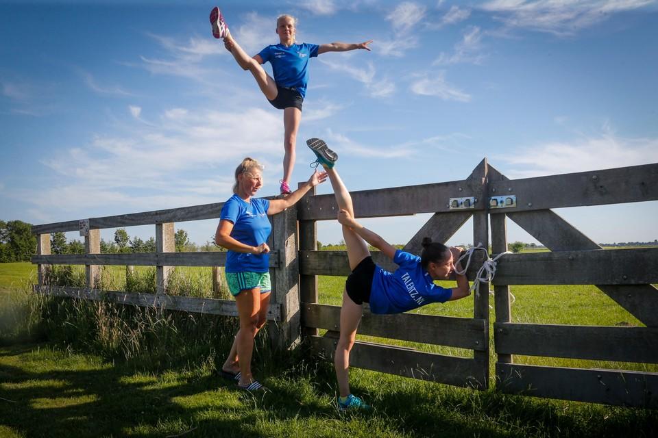 Trainster Monique Zwarthoed begeleidt de turnsters Mara Slippens en Sam van der Hilst (boven) tijdens hun oefeningen in de buitenlucht.