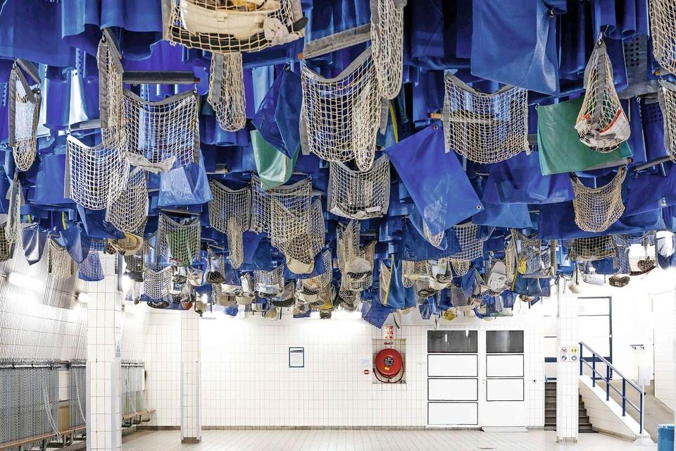 De netten met kleding hangen als vleermuizen aan het plafond.