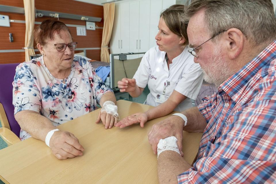 Verpleegkundig specialist Marlies Niesing laat aan patiënten Ali van Leenen en Kees Meijvogel de sensor zien die ze geïmplanteerd krijgen.