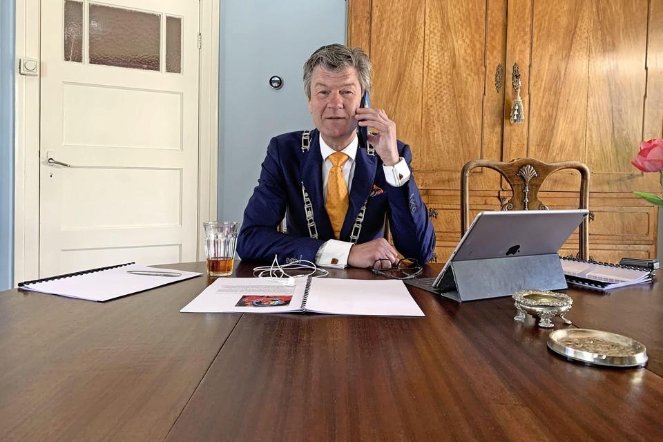 Burgemeester Toon Mans van Castricum belt met een van de gedecoreerden.