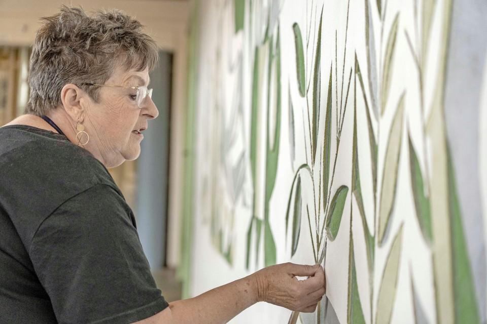 Janneke de Regt is bezig met het restaureren van de wanddecoratie.