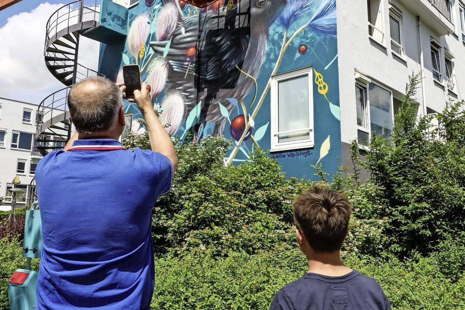 Rene Kramer en zijn kleinzoon Mees Tielman bewonderen gevel 4, waaraan Van der Sluijs nog werkt.