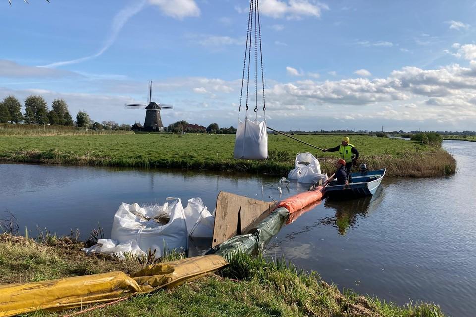 Aanleg van damwand met rijplaten en 'big bags'. Op de achtergrond de Tweede Broekermolen.