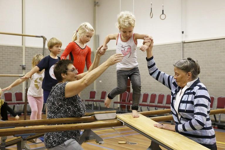 De kleuters dwarrelen over de vloer en de 83-jarige Marie Molenaar slingert nog soepel aan de ringen heen en weer; Gymvereniging Callantsoog is 50 jaar oud maar nog springlevend [video]