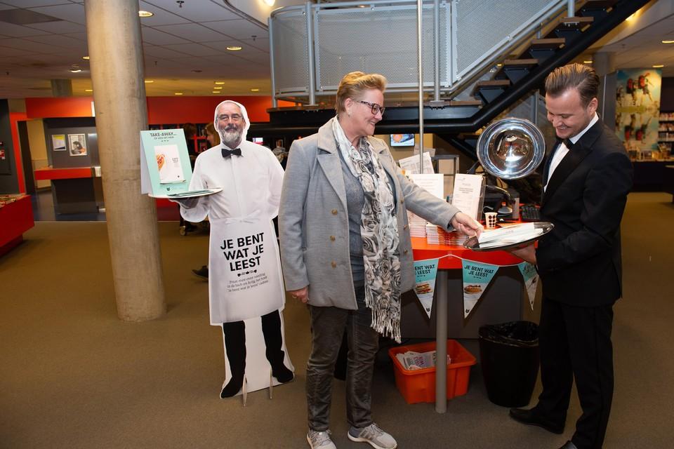 Ober Frank Kruit biedt Paula Bakker een boek aan in het kader van Nederland Leest.