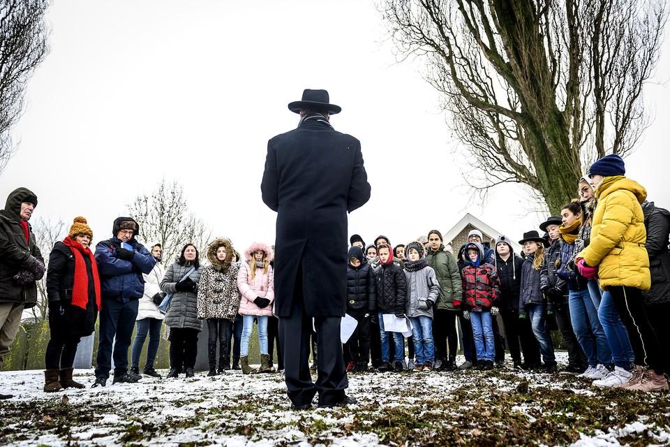 De rabbijn houdt een toespraak en trotseert samen met de kinderen de kou tijdens de herdenkingsdienst op de Joodse Begraafplaats.