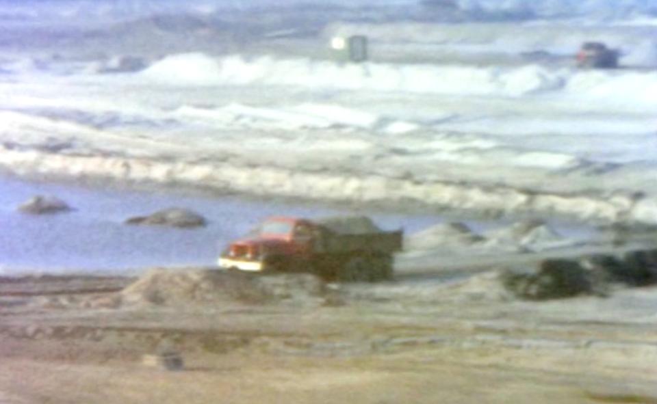 Vrachtwagens met zand rijden af en aan.