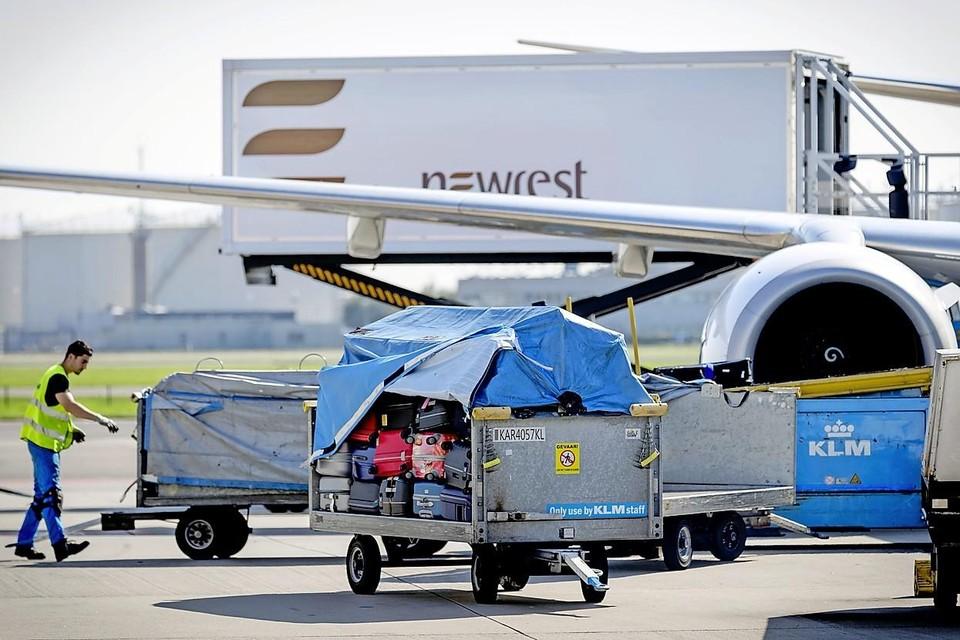Een medewerker met een bagagekar op het platform van luchthaven Schiphol.