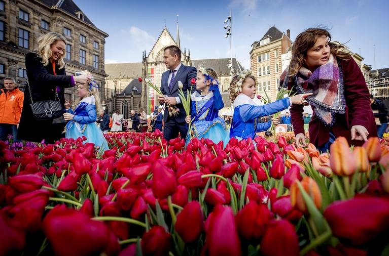 In de rij voor gratis bosje tulpen op de Dam in Amsterdam