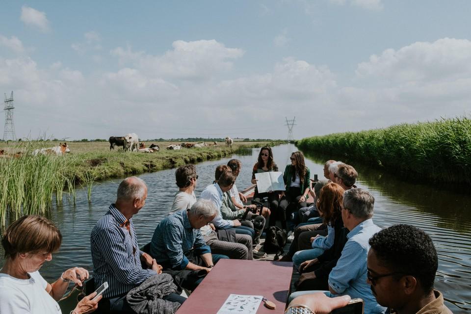Per boot door het veenweidegebied bij Ilpendam, discussiërend over het landschap van Laag Holland.