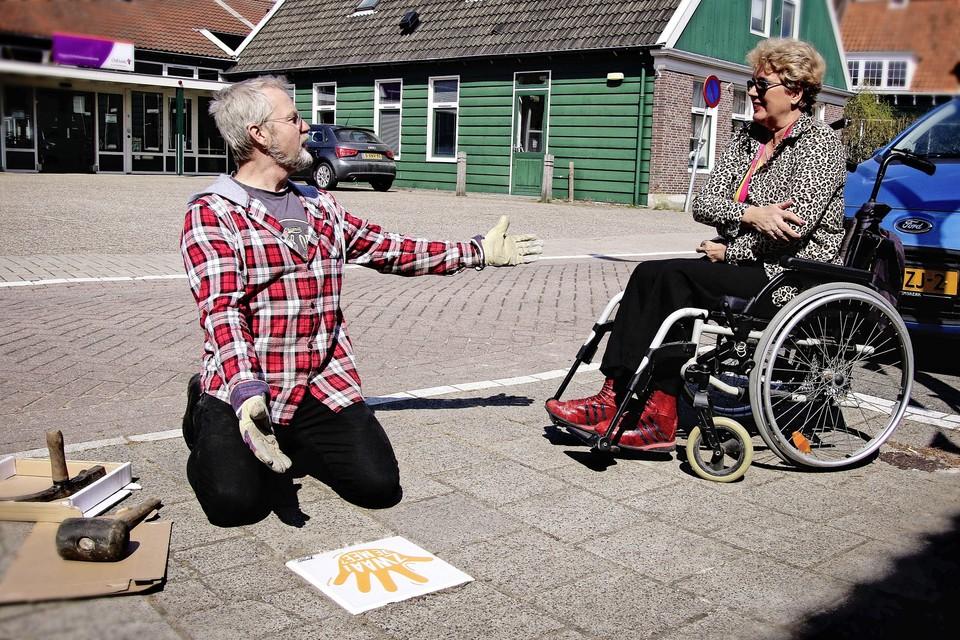 Gerrit Gelderman plaatst de zwaaitegel terwijl Bianca, woonachtig bij Odion in Krommenie, tevreden toekijkt