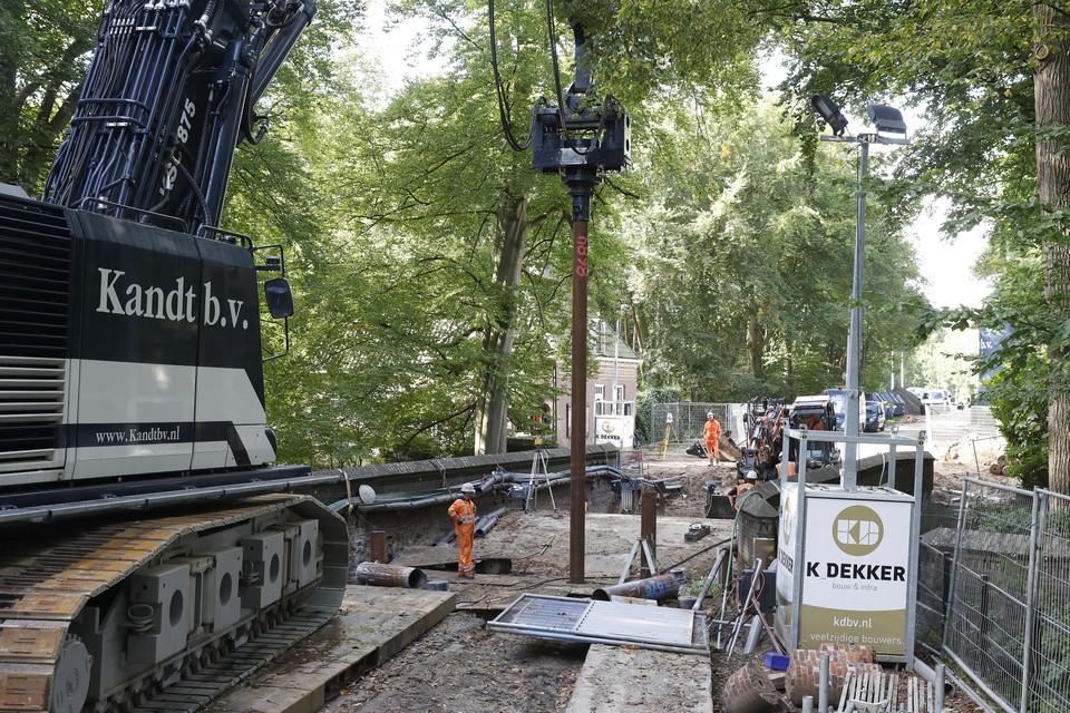 Metalen buizen van minimaal tien meter worden in de grond gezet ter verankering van het nieuwe wegdek.