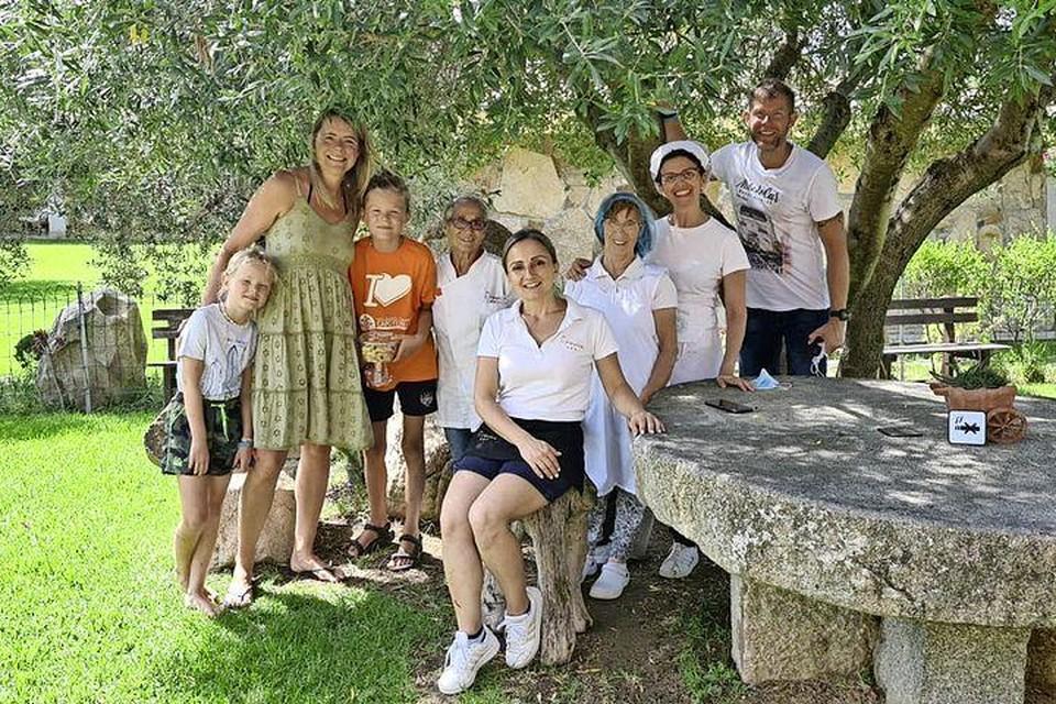 Het gezin uit Warmenhuizen met het personeel van de Agriculturo. Afke Bleeker in groene jurk omarmt haar kinderen Jik en Julie, uiterst rechts partner René.