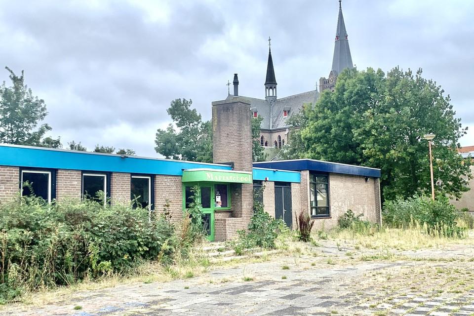 Een vleugel van de Mariaschool in Noord-Scharwoude met op de achtergrond de kerk.