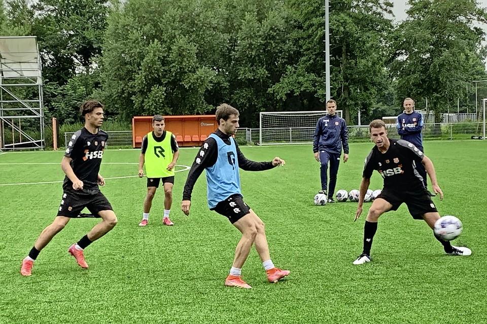 Gaetano Oristanio (blauw hesje) in duel met Sjors Kramer (rechts) en Denso Kasius tijdens de training.
