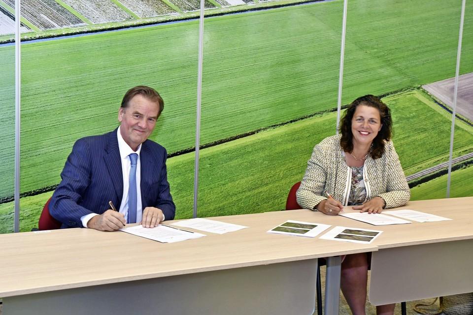 Wethouder Andrea van Langen van de gemeente Medemblik (rechts) tekent samen met de projectontwikkelaar het akkoord voor woningbouw in Hauwert.