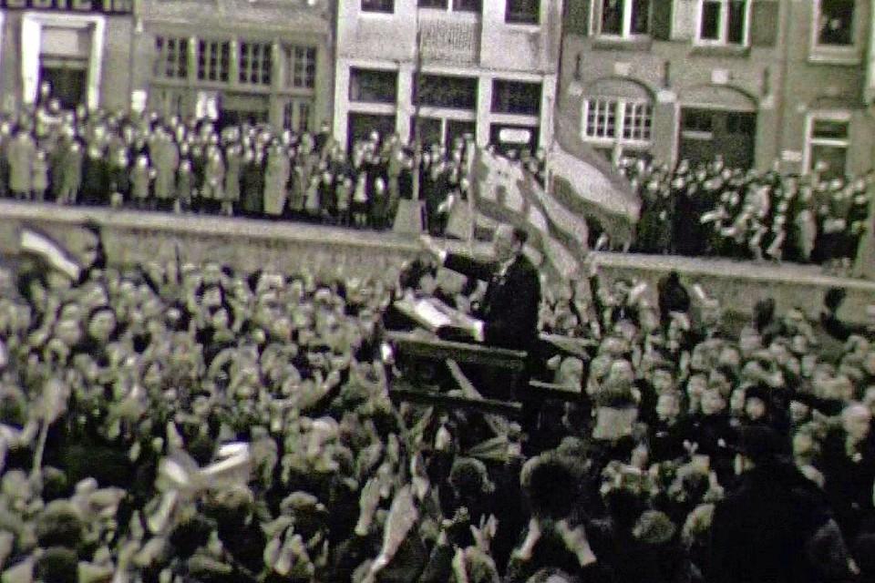 De Nederlandse en Alkmaarse vlag wapperen in de winterse wind terwijl duizenden zich hebben verzameld op en rond het Waagplein. De dirigent juicht, hoeden gaan in de lucht en het Wilhelmus moet hebben geklonken.