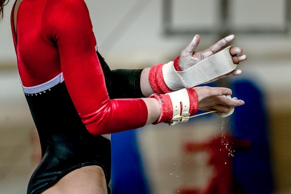 Een turnster poedert haar hand met magnesium.