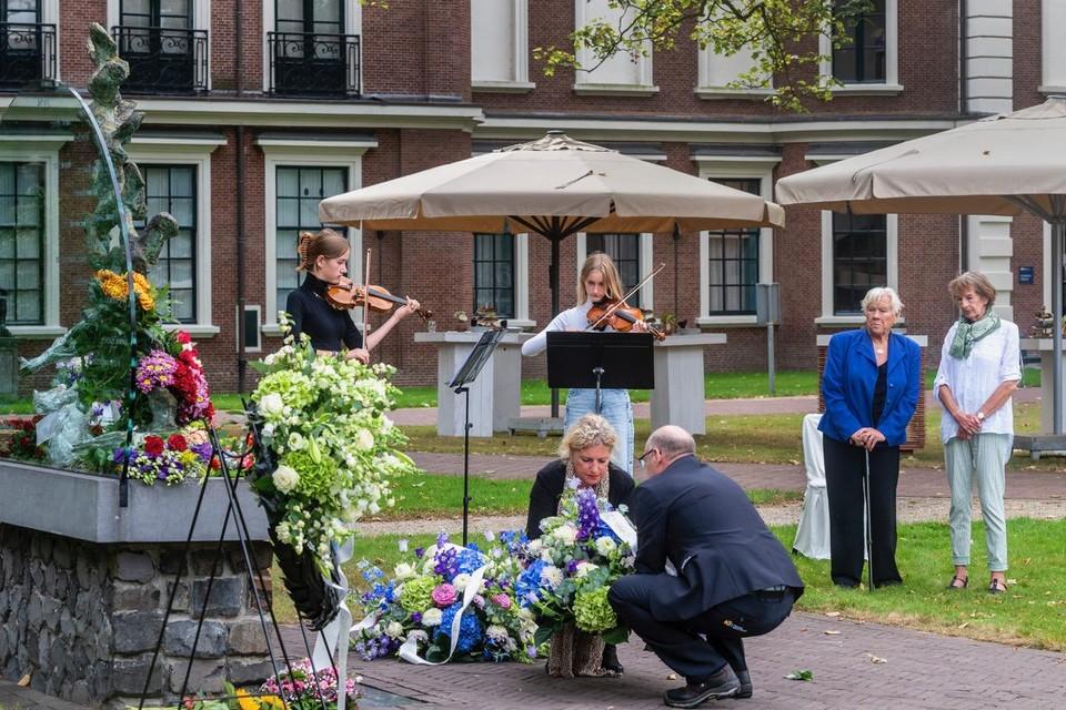 Provinciemedewerkers leggen een krans bij het monument terwijl Erin en Lute de Vos viool spelen. Rechts hun grootmoeder en mevrouw Zwager-Schriemer.