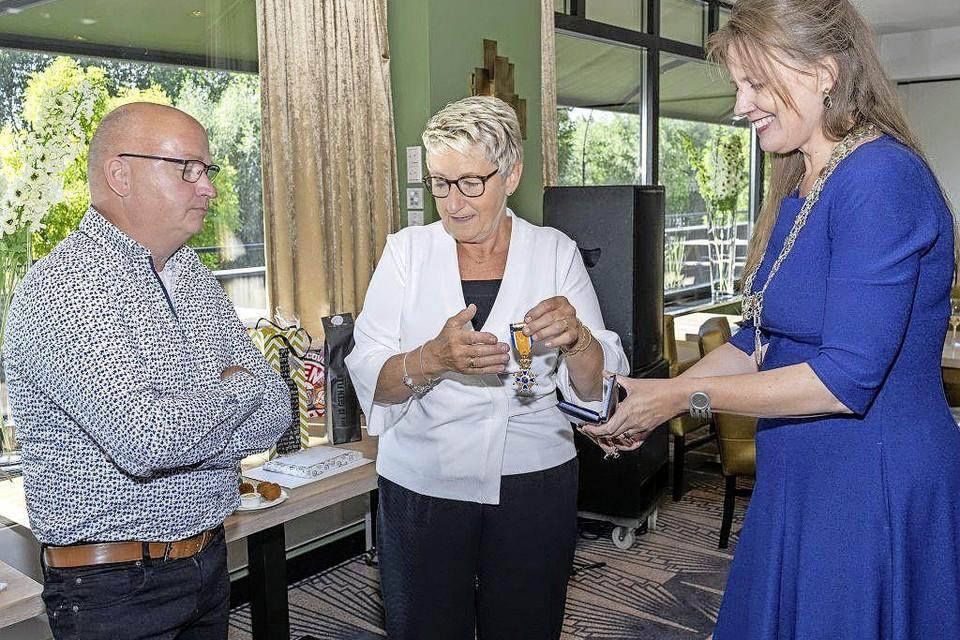 De burgemeester reikt via Van Wieringens partner de onderscheiding uit.