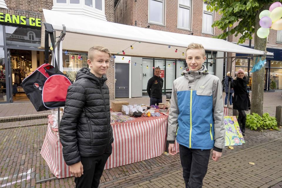 Stijn Koenis (links) en Mika Broers voor de kraam. Op de achtergrond houden docenten Koos Keijzer en Evelyne Koijman (uiterst rechts) een oogje in het zeil.