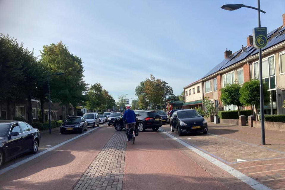 Een fietser op de Dorpsstraat moet uitwijken voor een auto die vanwege de blokkade omkeert.