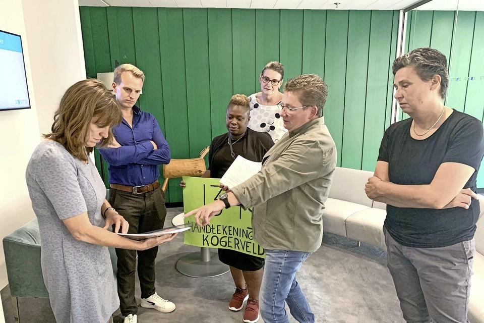 Bewoners van Kogerveld geven de handtekeningen aan Natasja Groothuismink.