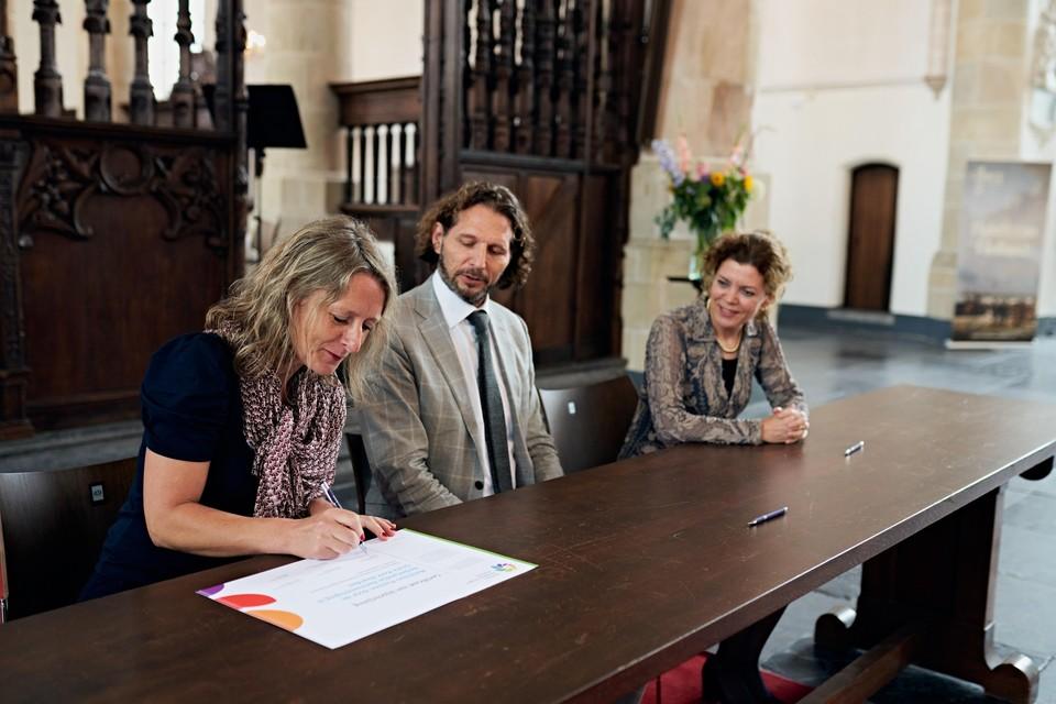 Ondertekening door Ellen Snoep, directeur van Stichting Grote Kerk Naarden. Rechts Willemijn Mooij van de Nederlandse Bachvereniging.