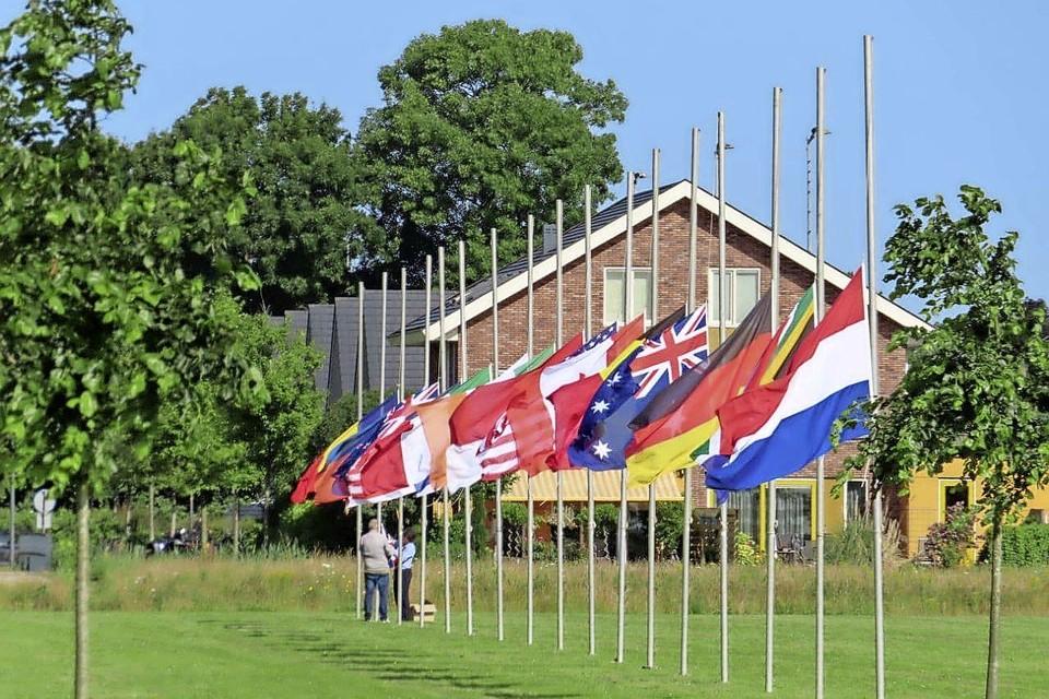 Elly van der Veek en Willem Koster van gemeente Haarlemmermeer zijn een uur bezig om alle 17 vlaggen plechtig halfstok te hangen