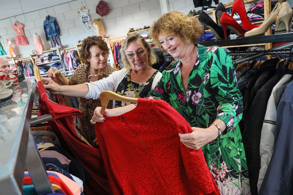 Astril, Hanja en wethouder Lydia Groot bekijken kleding uit de winkel.